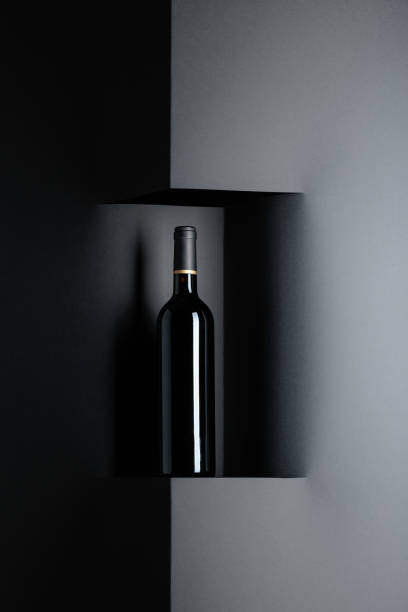 Unopened bottle of red wine on a black background. Copy space. stock photo