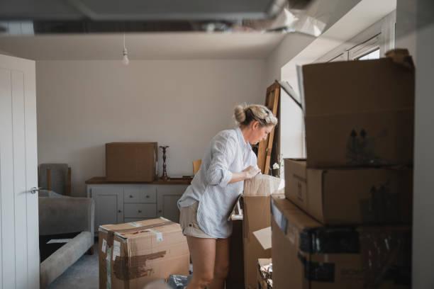 unpacking boxes in her new home - oggetti personali foto e immagini stock