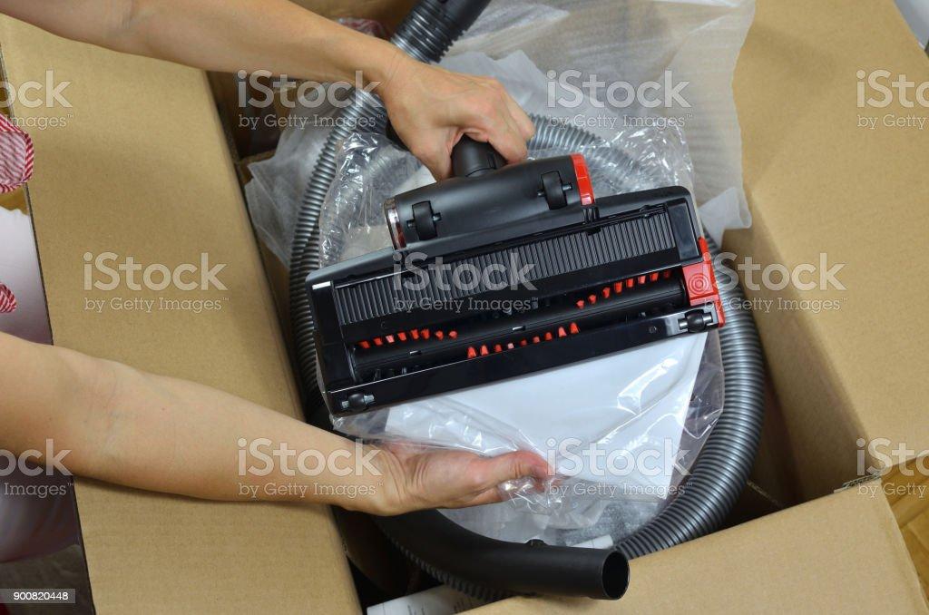 Unpacking new modern vacuum cleaner stock photo