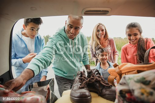 Inside view of car boot as family unpack the car.