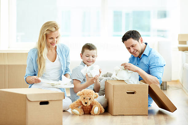 unpacking things - happy mom packing some toys stock photos and pictures