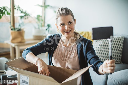 Women unpacking workout equipment ordered online while in home isolation during quarantine, she making video for social media. Stay home we deliver sign on box.