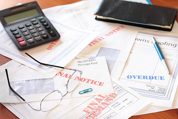 Unpaid Bills on Table with Calculator stock photo