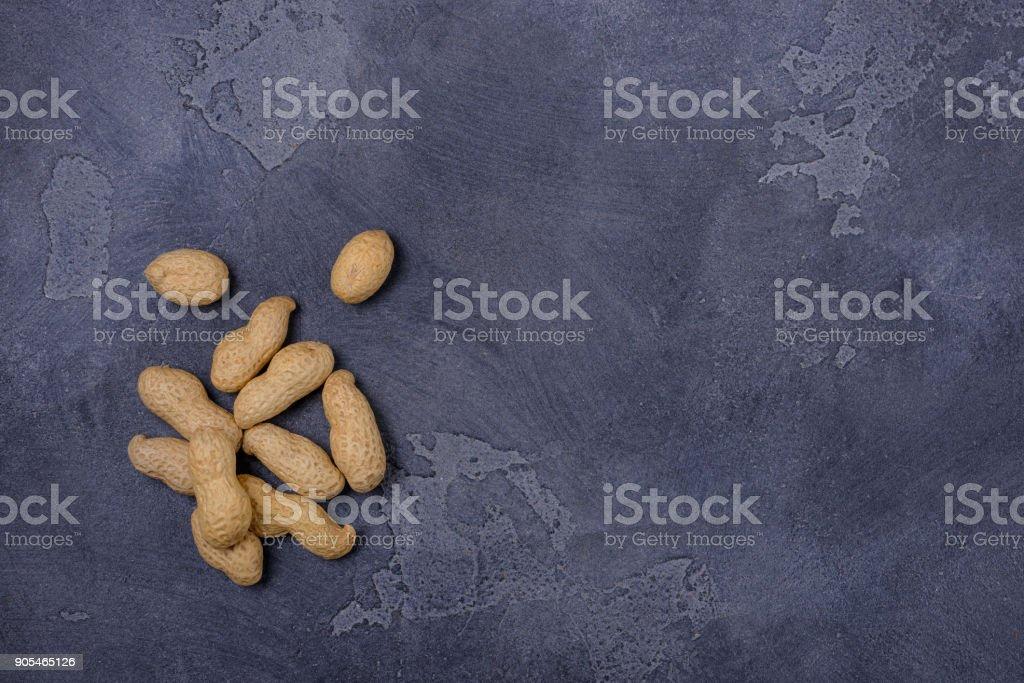 Unpeeled  peanuts on dark stone background stock photo