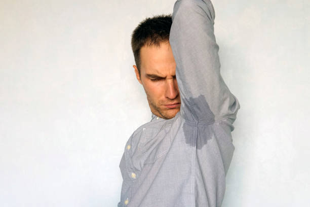 Unpleasant smell of sweat. Dissatisfied expression on his face. wet spot on my blue shirt from sweat. man sniffs sweaty armpits on a blue background. Copy space stock photo