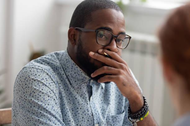 onaangenaam verraste afrikaans-amerikaanse zakenman die vrouwelijke kaukasische medewerker luistert - achterdocht stockfoto's en -beelden