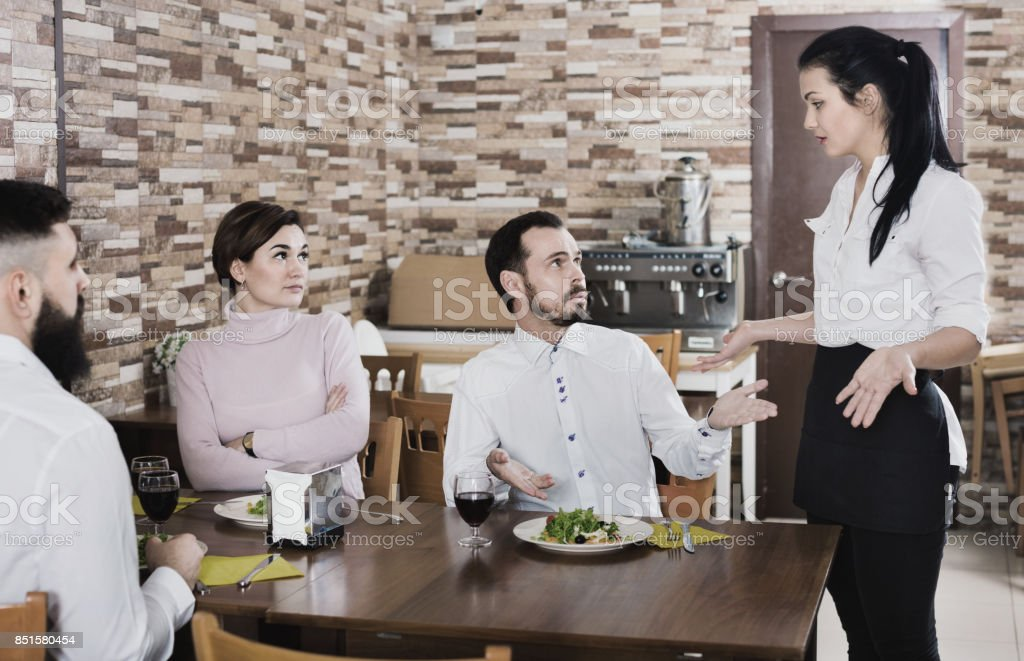 Unpleased client talking with manager in restaurant Young ordinary couple doesn't like the service and food at cafe Adult Stock Photo