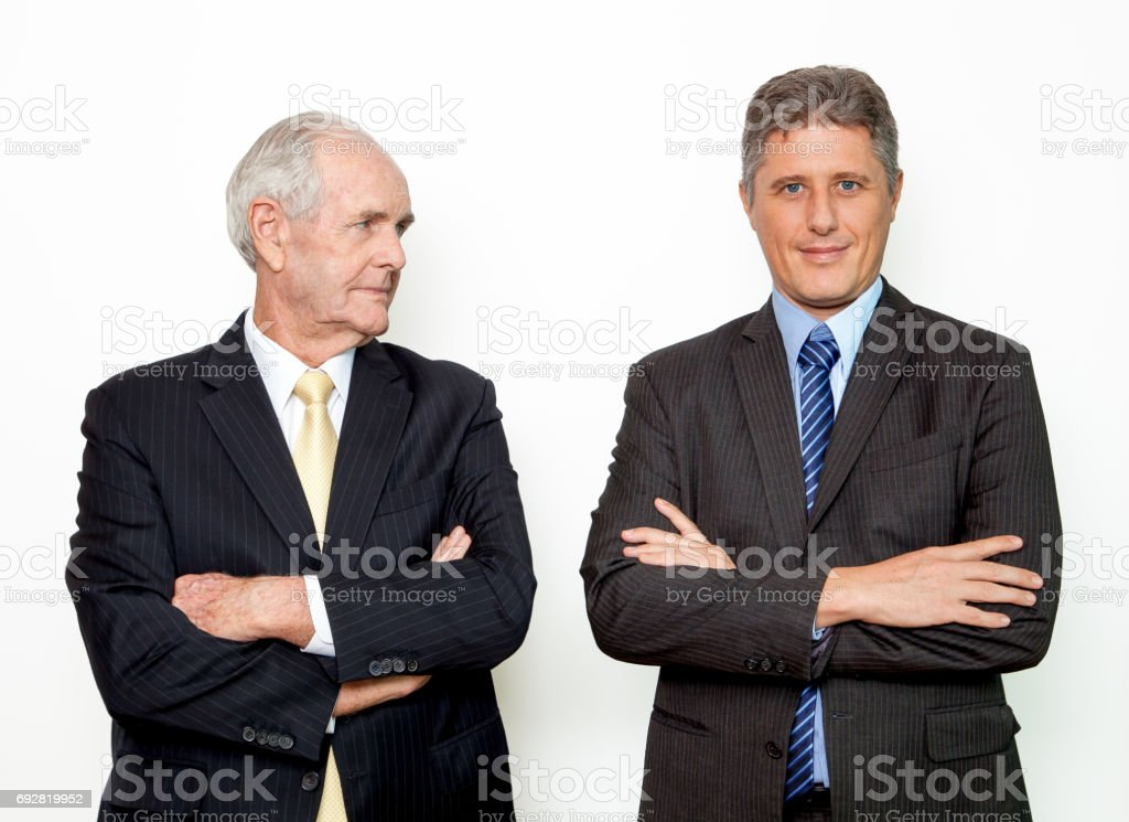 Unpleased senior man looking at colleague stock photo