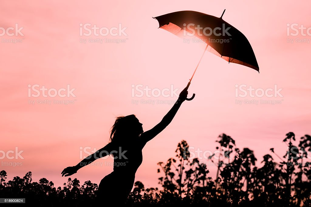 Unplugged free silhouette woman with umbrella fly to future stock photo