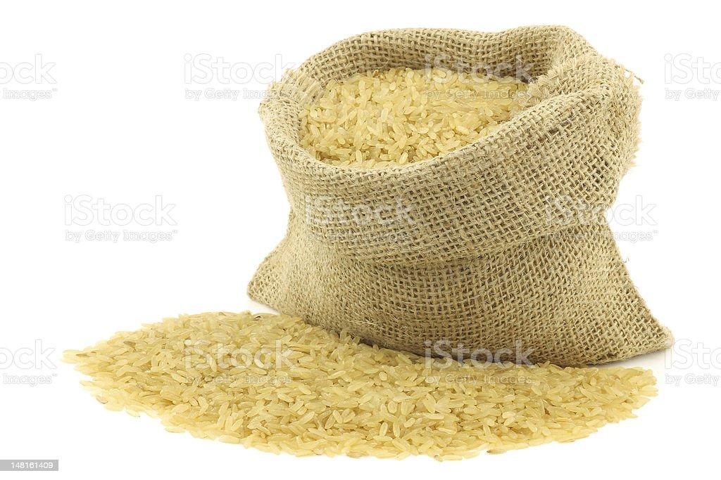 unpolished rice (whole grain) in a burlap bag stock photo