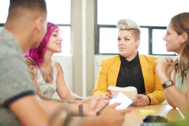 ungestellte gruppe von kreativen unternehmern in einem offenen konzept büro brainstorming zusammen auf einem digitalen tablet - tattoo ideen stock-fotos und bilder