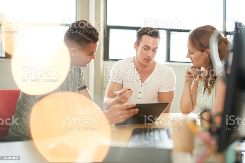 Unposed group of creative business entrepreneurs in an open concept office brainstorming together on a digital tablet stock photo