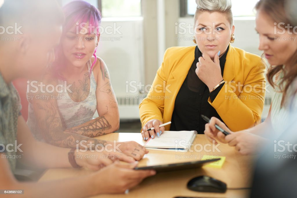Unposed group of creative business women entrepreneurs in an open concept office brainstorming together on a digital tablet stock photo