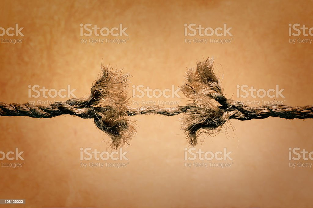 Unraveling rope about to break against brown background stock photo