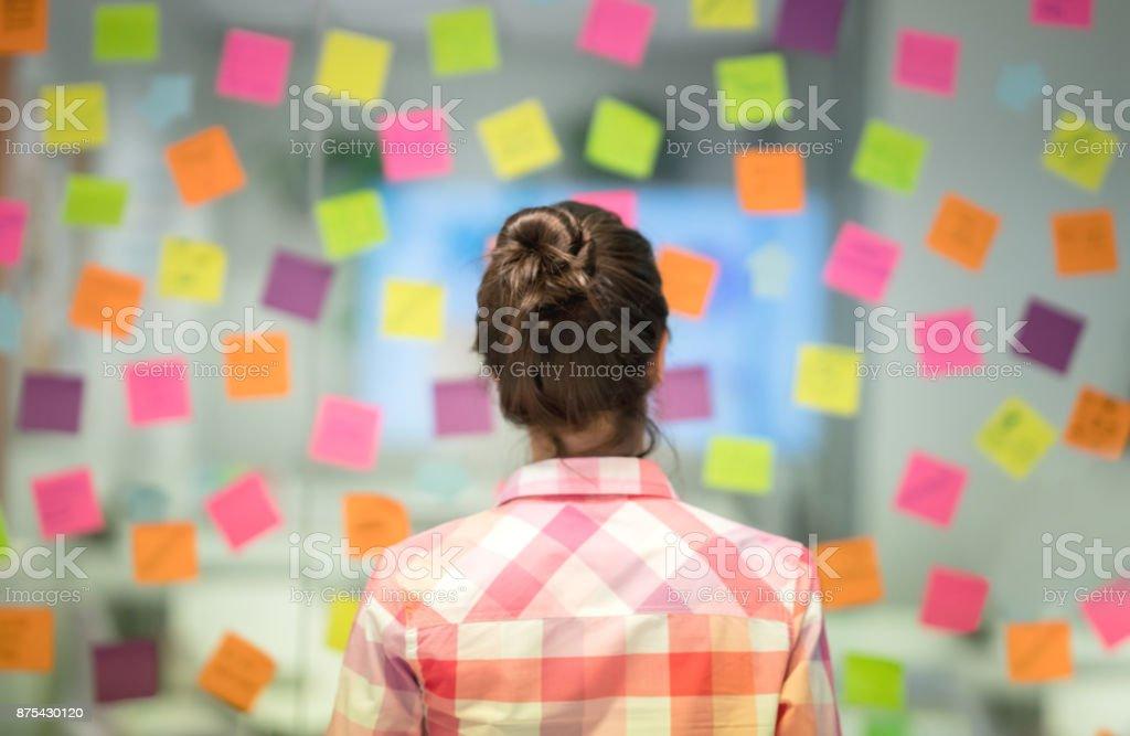 Unrecoginzable Frau im Büro denken Ideen für das Geschäft mit Klebstoff Noten – Foto