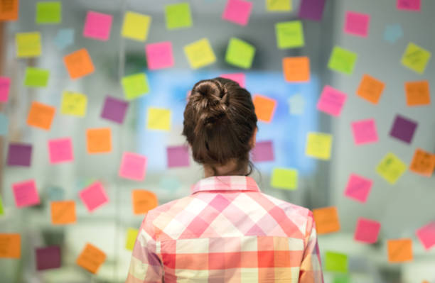 unrecoginzable woman at the office thinking ideas for the business using adhesive notes - post it foto e immagini stock