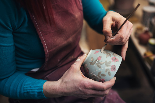 Unrecognisable female potter decorating  a clay pot in her workshop.