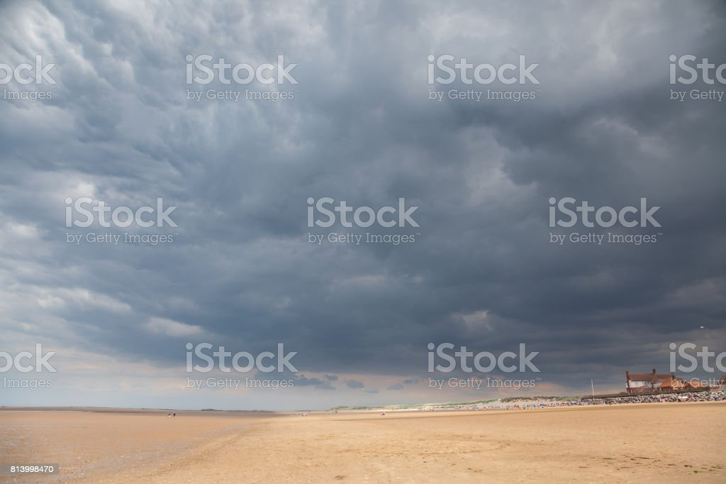 unrecognisable people under storm clouds and sun on beach at Brancaster Norfolk England stock photo