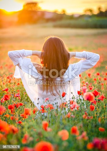 spanish unrecognisable woman in a poppies field at sunset from behind