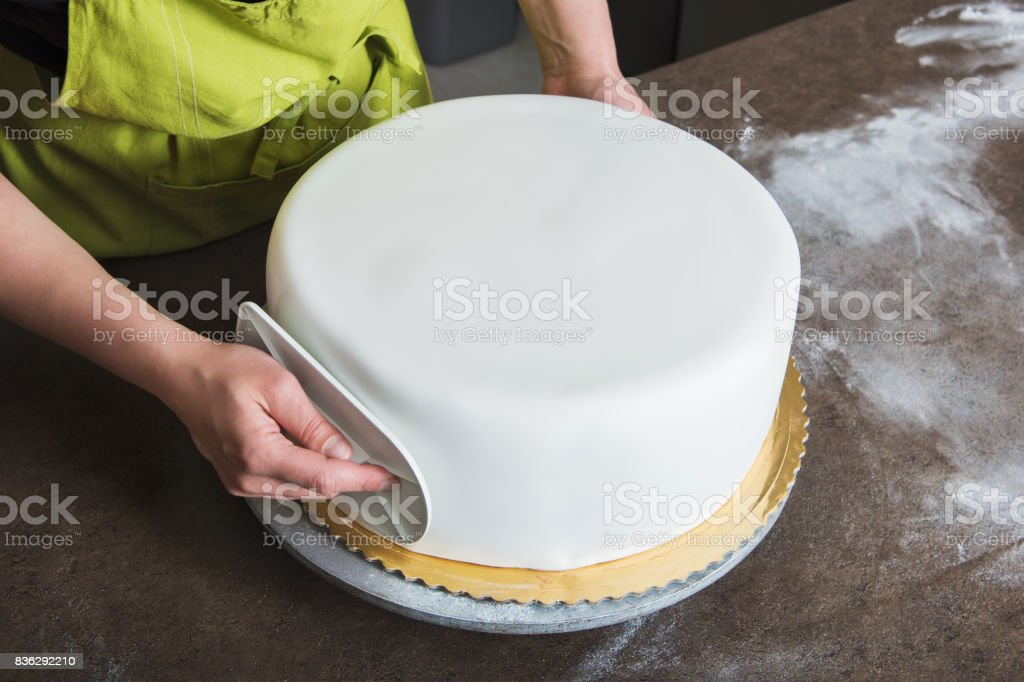 Unrecognisable woman in bakery decorating wedding cake with white fondant stock photo