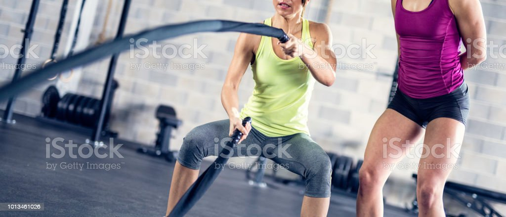 Panoramic photo of a woman swinging battle ropes while her personal...
