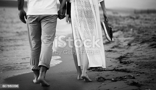 139880782 istock photo Unrecognisible Couple Walking On The Beach 607880096