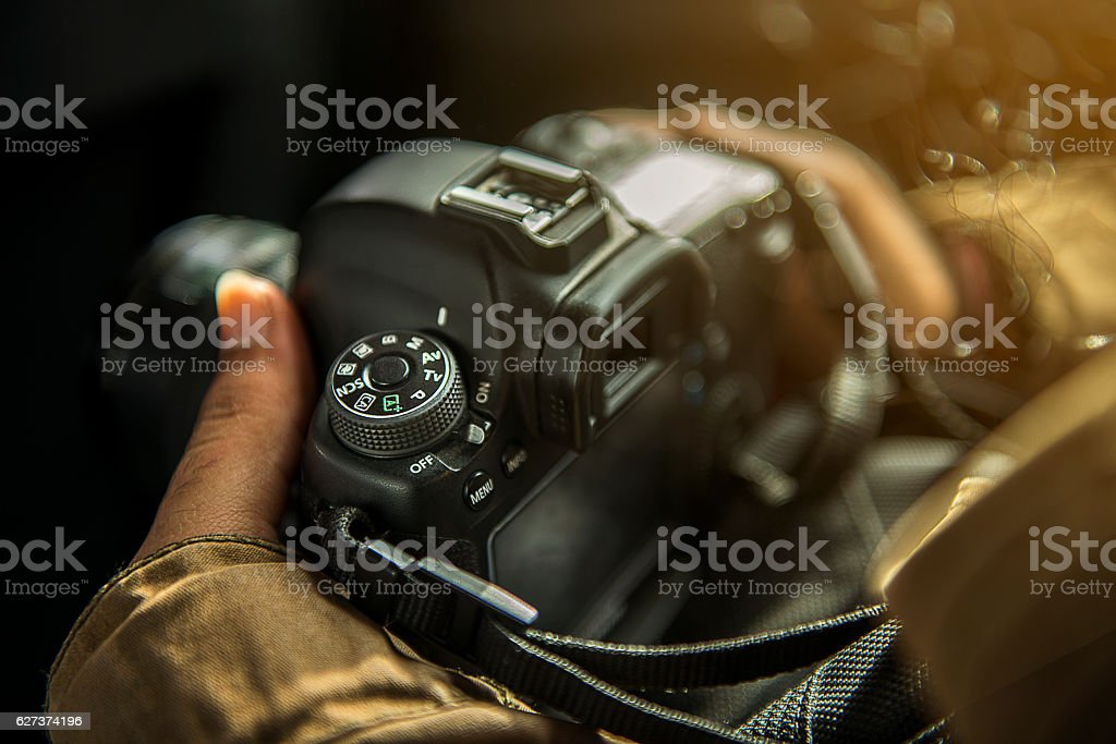 Unrecognizabe person holding a DSLR camera stock photo