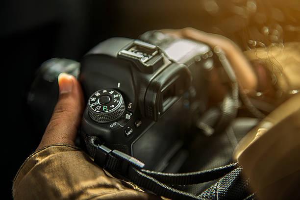 Unrecognizabe person holding a DSLR camera stock photo