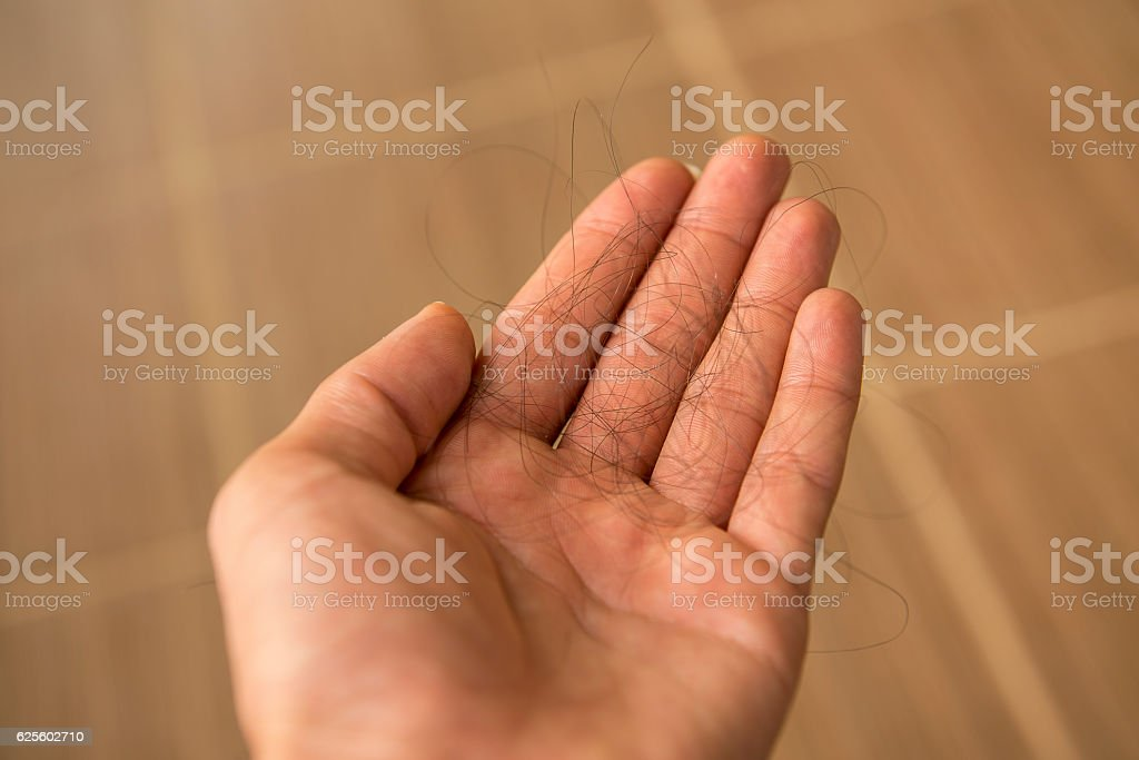 Unrecognizabe person holding spilled hairs stock photo