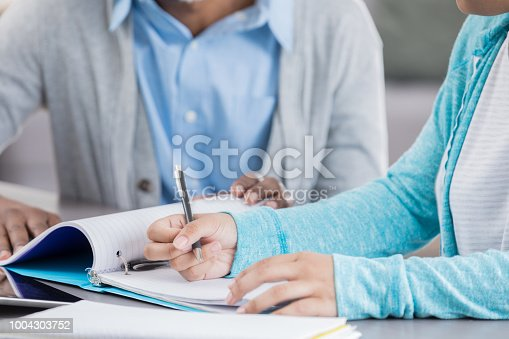 An unrecognizable adult and teenage girl sit at a desk in front of a note pad and binder.  The teen writes in the note pad as the adult holds the pages down.