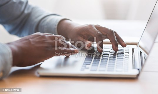 Hands of unrecognizable african american businessman typing on laptop keyboard in office, closeup with copy space, panorama