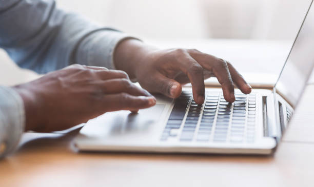 Unrecognizable african american man typing on laptop keyboard in office Hands of unrecognizable african american businessman typing on laptop keyboard in office, closeup with copy space, panorama typing stock pictures, royalty-free photos & images