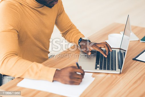 Doing Research. Unrecognizable black businessman working on laptop, browsing information and writing report, free space