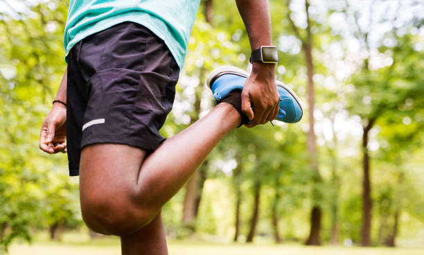 Unrecognizable afro-american man in park stretching legs. stock photo
