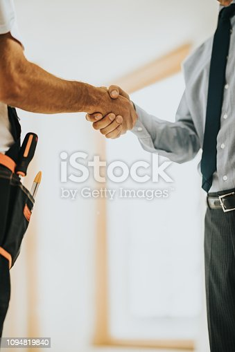 961745166istockphoto Unrecognizable architect shaking hands with manual worker construction site. 1094819840