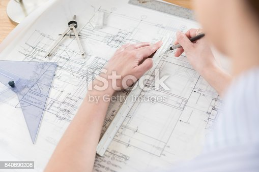 istock Unrecognizable architect uses ruler for technical drawing 840890208