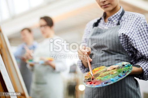Mid section portrait of unrecognizable female artist holding palette mixing oil colors while painting picture on easel in art studio, copy space