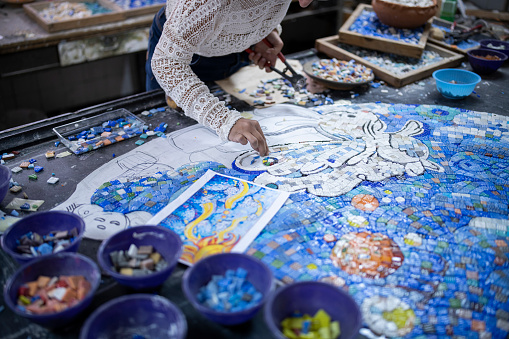 Unrecognizable woman artist making art project with mosaic smalth.