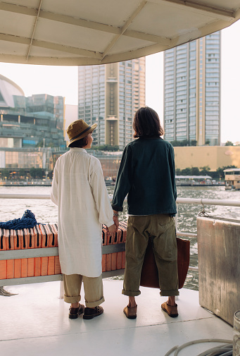 A back view shot of an anonymous Thai couple standing by the river and holding hands in the city.