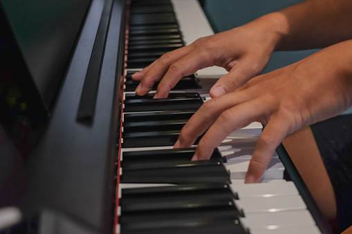 Close-up shot of Asian male hands practicing a classical composition on piano keys. He's playing piano at home.