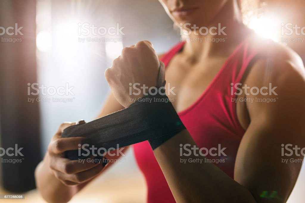 Irreconhecível atleta aplicar bandagem adesiva por lado antes do treino de boxe. - foto de acervo