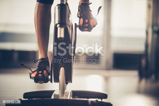 Unrecognizable athlete having a exercising class on stationary bike in a gym.