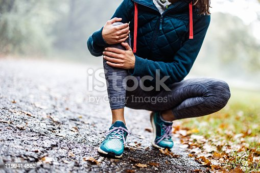 Unrecognizable athletic woman feeling pain in her knee at the park. Copy space.