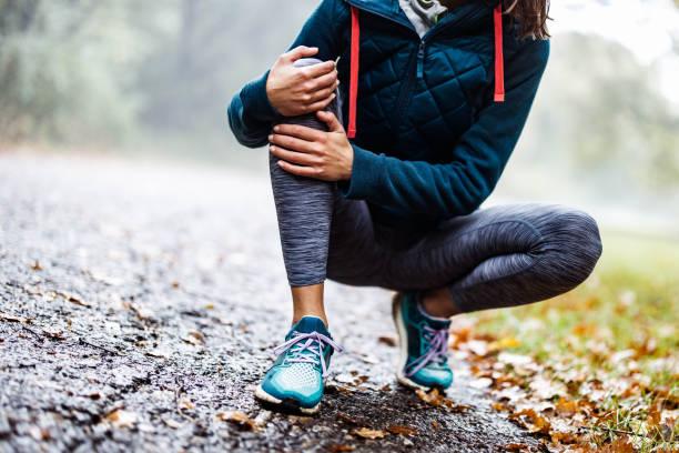 atleta irreconhecível segurando o joelho com dor no parque. - articulação humana - fotografias e filmes do acervo