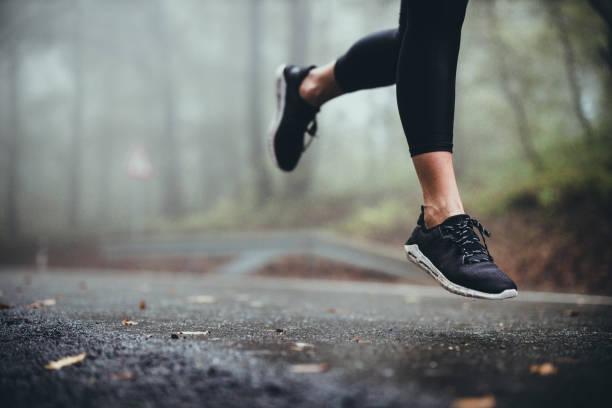 nierozpoznawalny sportowiec biegający po drodze w deszczowy dzień. - but sportowy zdjęcia i obrazy z banku zdjęć