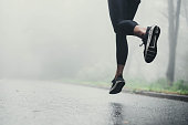 Unrecognizable athletic woman running on the road during foggy day in nature. Copy space.