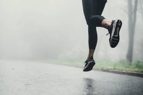 Unrecognizable athlete jogging on the road during rainy day. stock photo