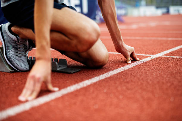 Unrecognizable Athlete Preparing For Start On Running Track. Unrecognizable Athlete Preparing For Start On Running Track. Young Muscular Male Athlete take a position on running track field. Low Section of Athlete on running track. track starting block stock pictures, royalty-free photos & images