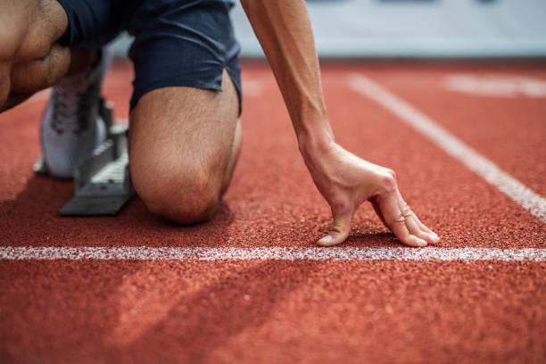 athlète méconnaissable se préparant pour le début sur la piste de course. - starting block photos et images de collection