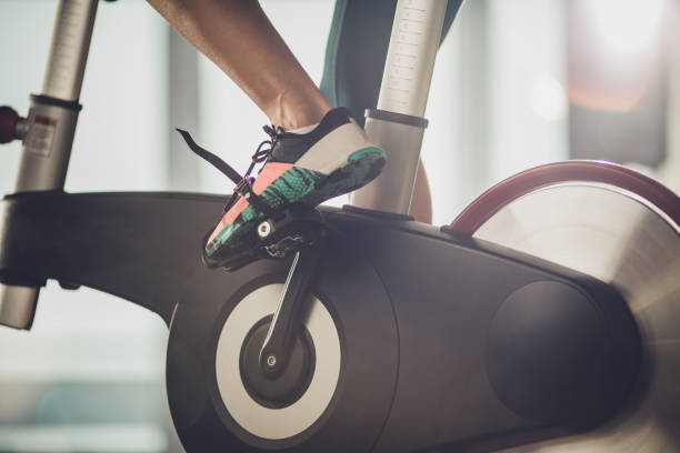 Unrecognizable athletic legs during exercising training in a health club. Close up of unrecognizable female athlete exercising on exercise bike in a gym. exercise bike stock pictures, royalty-free photos & images